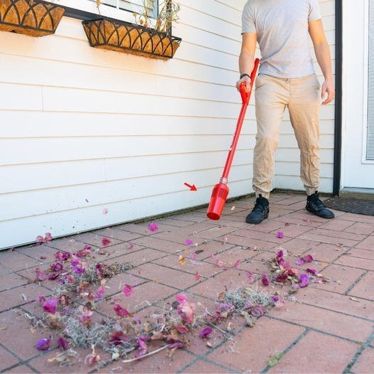 A man using the ZoomBroom on his sidewalk to get rid of leaves and other forms of debris to easily and efficiently clean this outdoor living area.