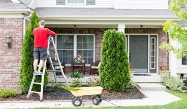 An image of a man on a ladder doing yardwork and outdoor chores to keep his outdoor living spaces clean and beautiful - ZoomBroom