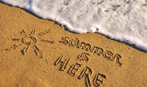 """An image of the words """"Summer is Here"""" written in the sand on a beach near the water - ZoomBroom"""