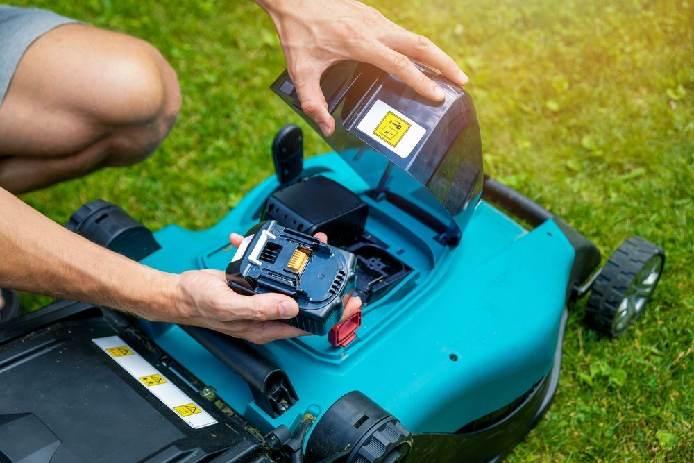 An image of a man putting a battery in a battery-powered lawn mower, which made the list for one of the best pieces of outdoor equipment to have in 2022.