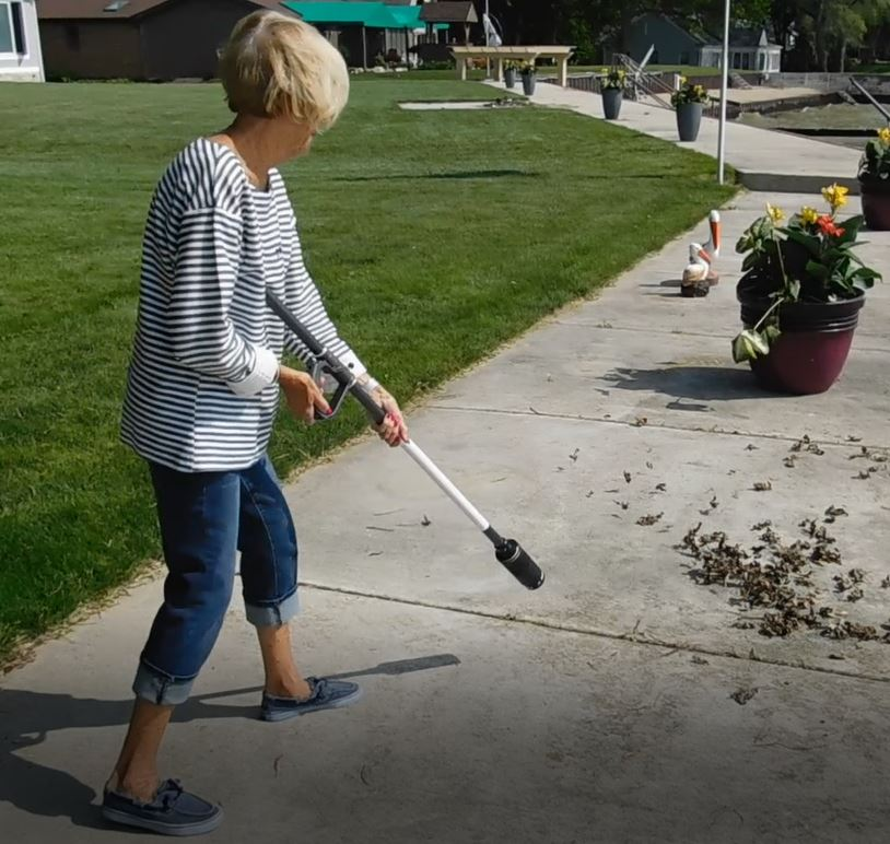 An image of an older lady using the ZoomBroom tornado to clear her sidewalk of leaves and debris - ZoomBroom