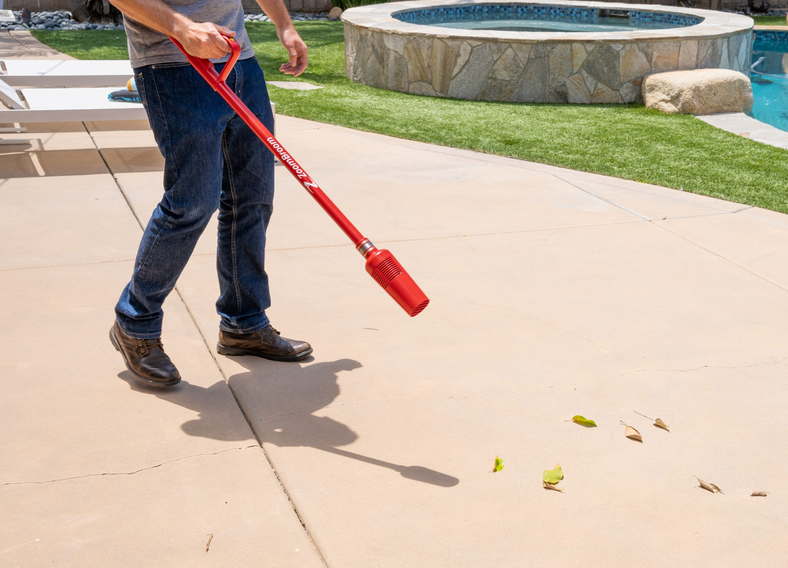 A man is using the ZoomBroom Tornado to blow away leaves and other debris off of his walkway.