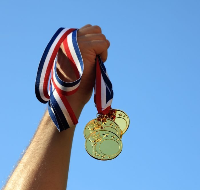 A man is holding up gold medals after winning first place in his sport - ZoomBroom