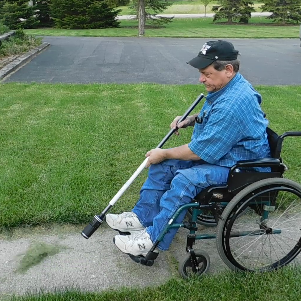 A man in a wheelchair is using the ZoomBroom Tornado to clear leaves and debris from his walkway.