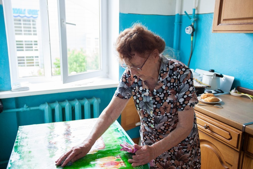 An elderly lady using cleaning products for seniors to clean her kitchen countertop. - ZoomBroom