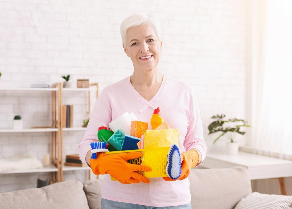 An elderly woman is holding a basket of cleaning supplies as she tries to easily clean her house with the most efficient tools for seniors. - ZoomBroom