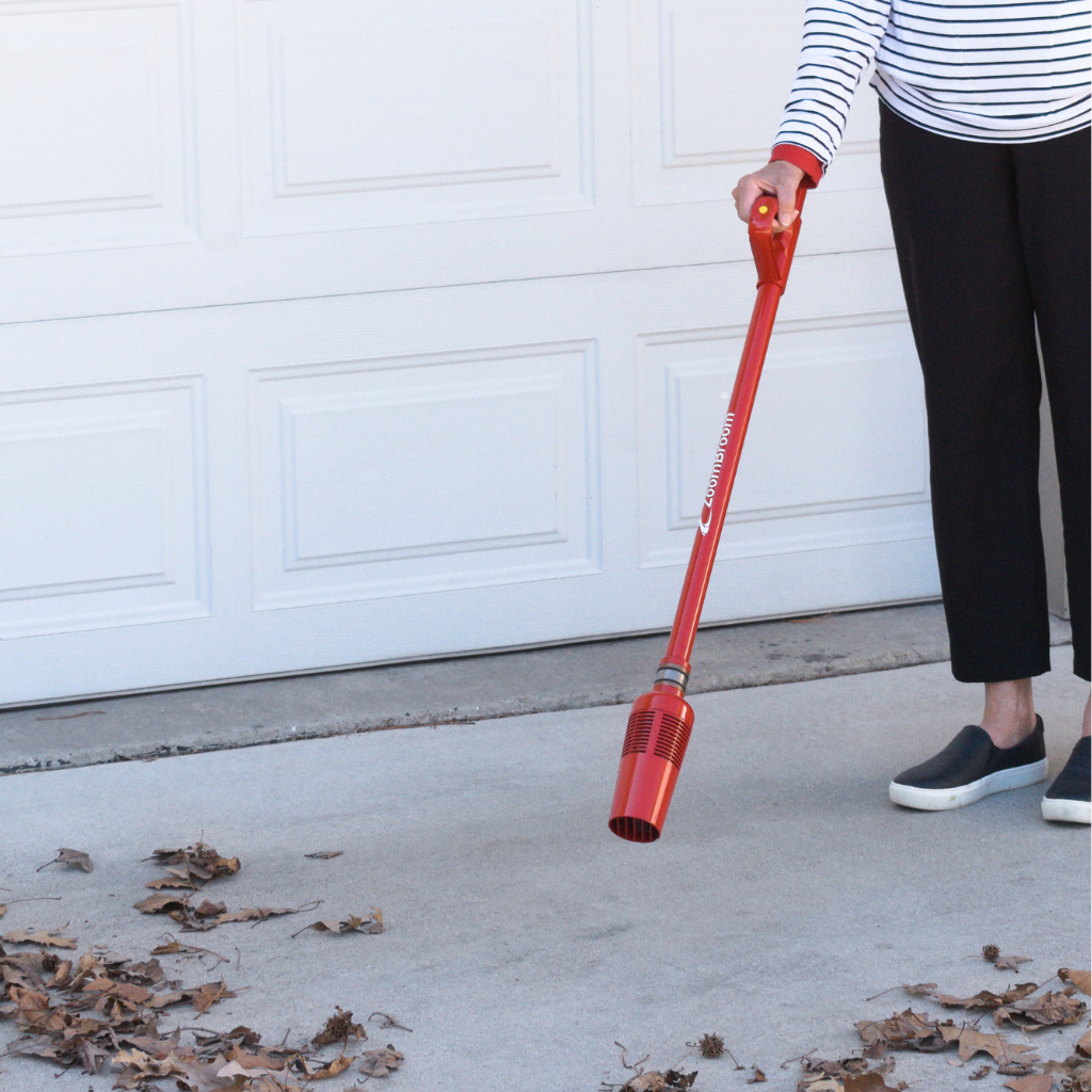 An elderly lady using the ZoomBroom Tornado to clear leaves and debris from her driveway. - ZoomBroom
