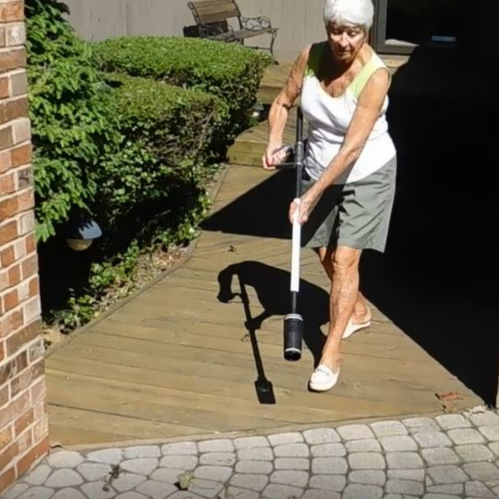 An older woman using the ZoomBroom Tornado to sweep away debris, leaves, and other impediments near her garden. - ZoomBroom