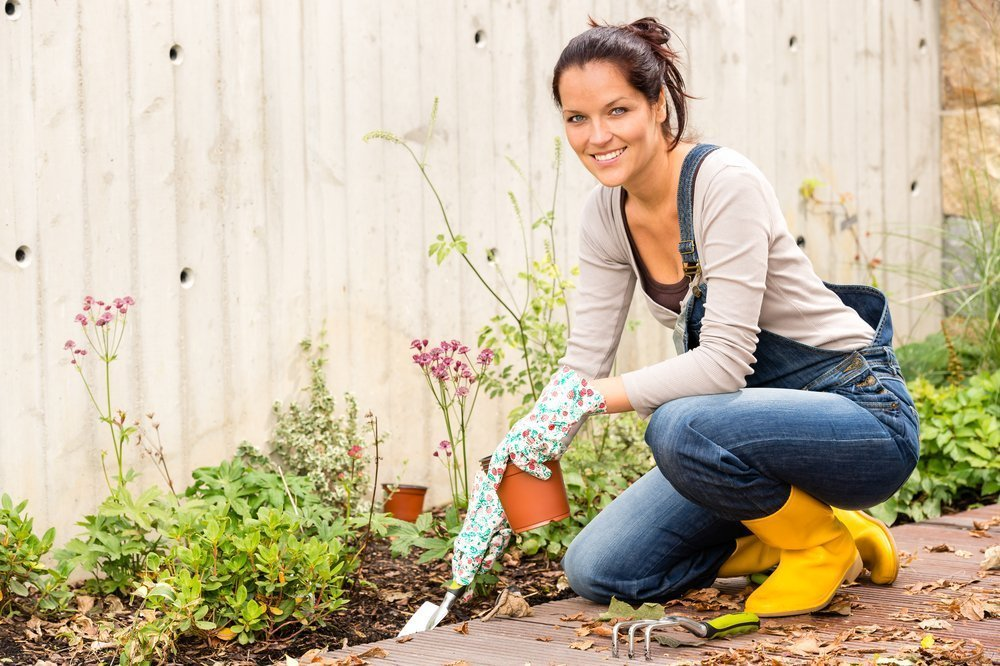 A young woman gardening with tools made specifically for women gardeners, like the ZoomBroom. - ZoomBroom