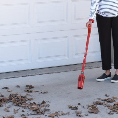 A woman using a ZoomBroom Tornado as a lightweight and cordless air broom to clear the leaves and other debris from her driveway. - Zoom Broom